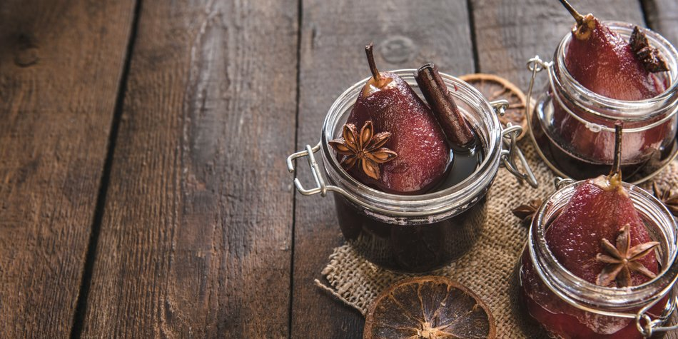 Sweet cooked pears and red wine served in the jars,selective focus and blank space