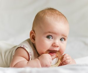 Six-month baby girl on her stomach with teether in the mouth