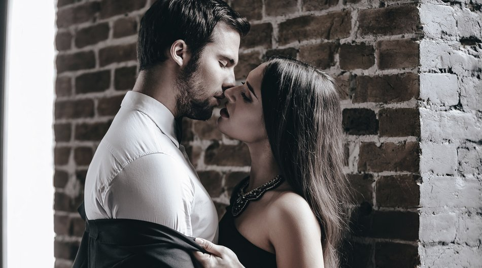 Close-up side view of beautiful young woman in cocktail dress kissing her boyfriend and taking off his jacket while standing near brick wall in loft interior