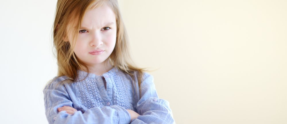 Little angry girl portrait at home