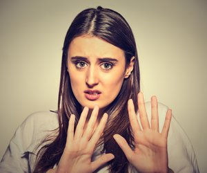 Closeup portrait of scared woman raising hands up in defense afraid about to be attacked or avoiding unpleasant situation, isolated on gray background. Negative human emotion facial expression feeling