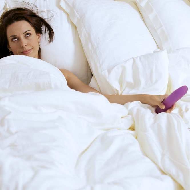 Young woman holding dildo on bed