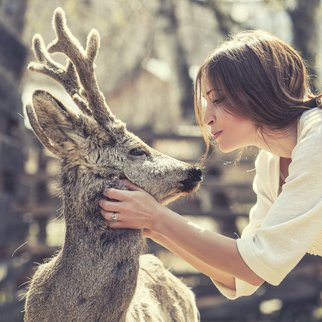 Young beautiful woman hugging animal ROE deer in the sunshine, protecting an animal