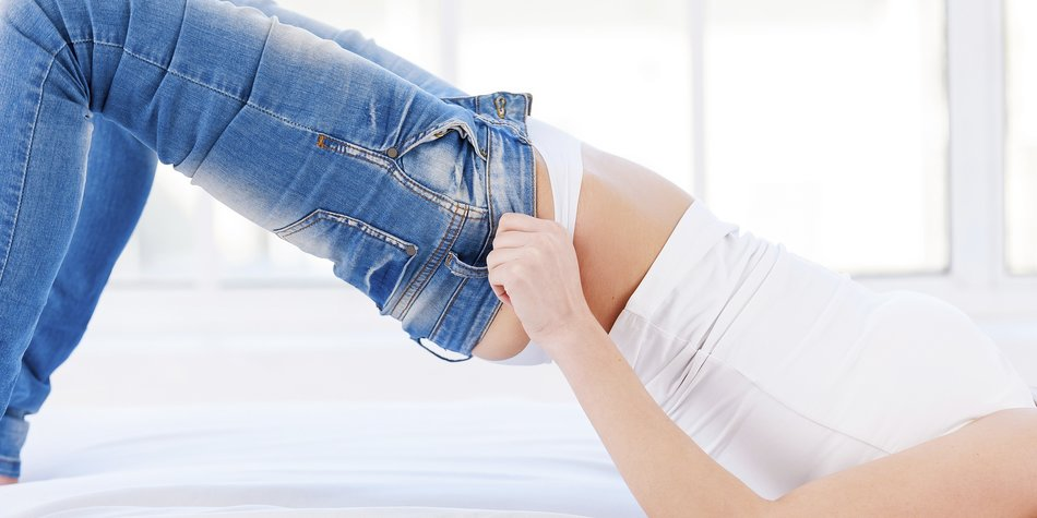 Cropped image of young blond woman lying on the bed and pulling on tight jeans