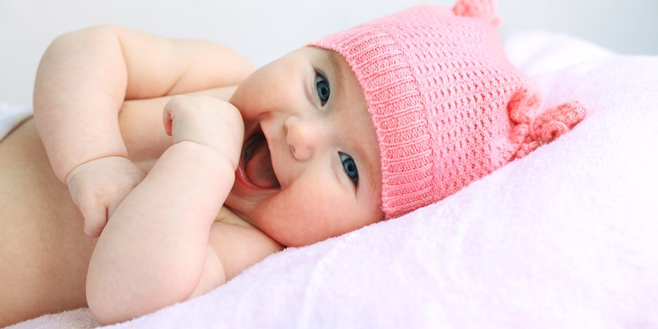 laughing european baby girl with big blue eyes in pink hat