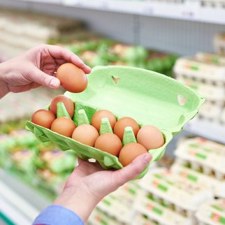 In the hands of a woman packing eggs in the supermarket