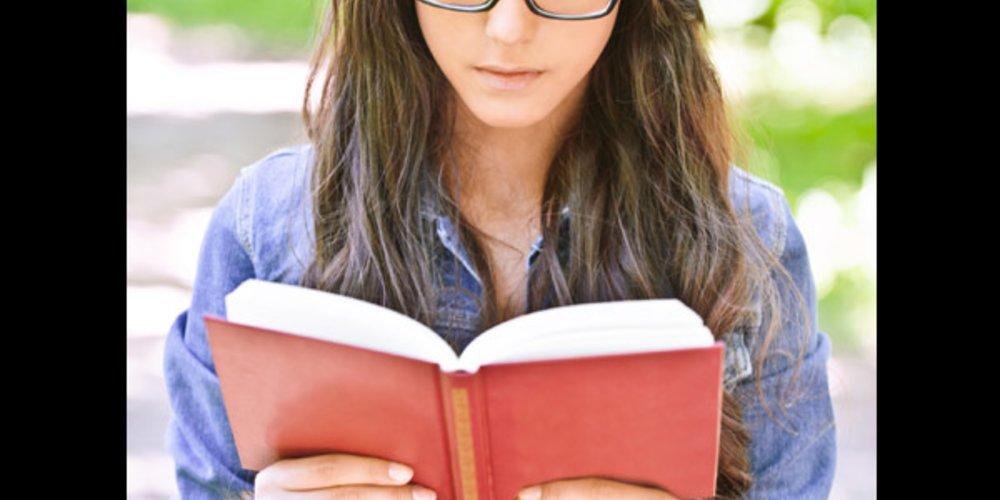 Brillenträgerin liest ein Buch