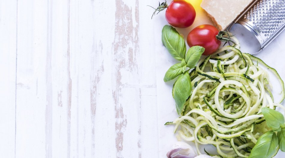 Zucchini spaghetti with parmesan and herbs on white table
