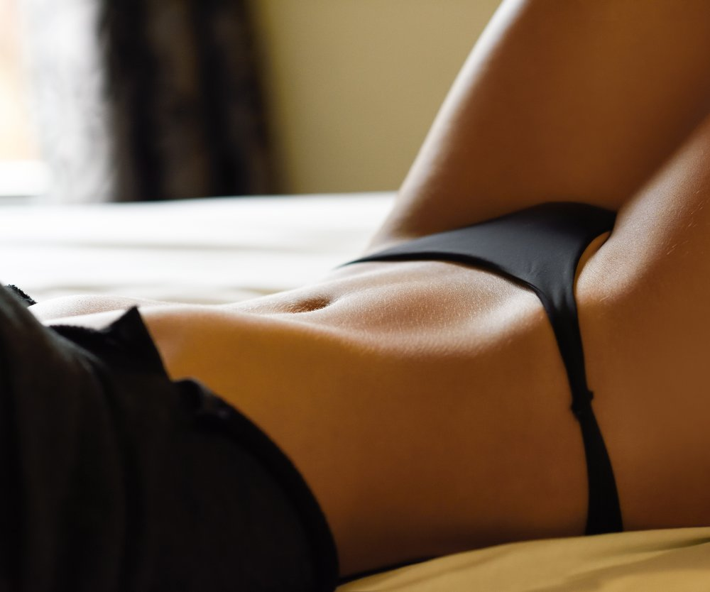 Sexy young woman in lingerie posing on the bed