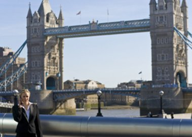 Eine Frau telefoniert vor der Tower Bridge in London