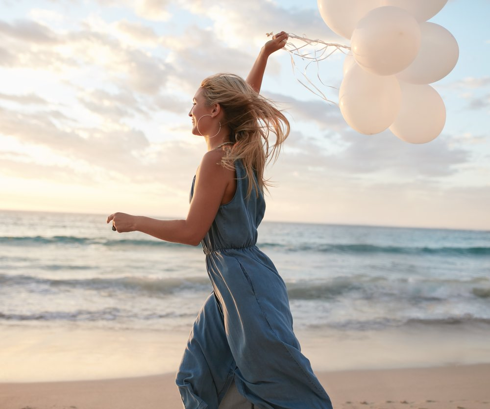 Side view shot of beautiful young woman running on the beach holding balloons. Female running on the sea shore and having fun.