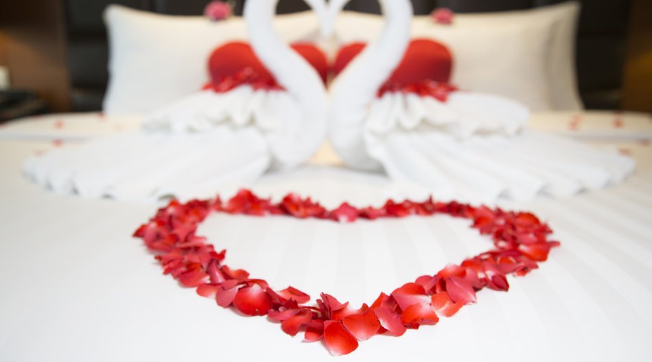 Two swans (made from towels) form a heart on a hotel suite bed, with flowers surrounding them.