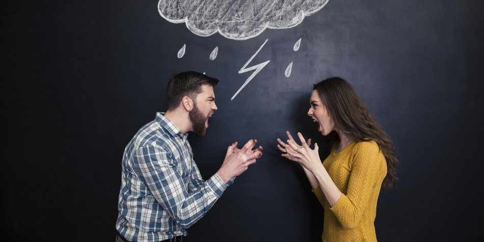 Quarrelling young couple standing against background of chalkboard and screaming on each other