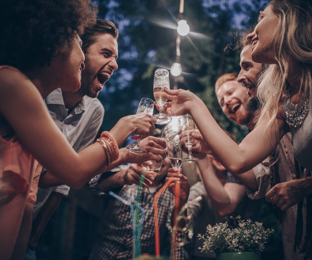 Low angle view of large group of happy people having fun while toasting with alcohol on a night party.