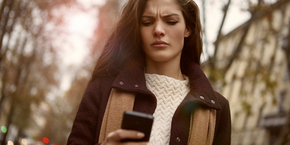 Woman texting with someone, and finds the message strange
