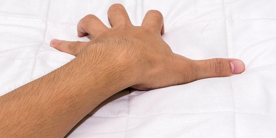 hand grasping sheets