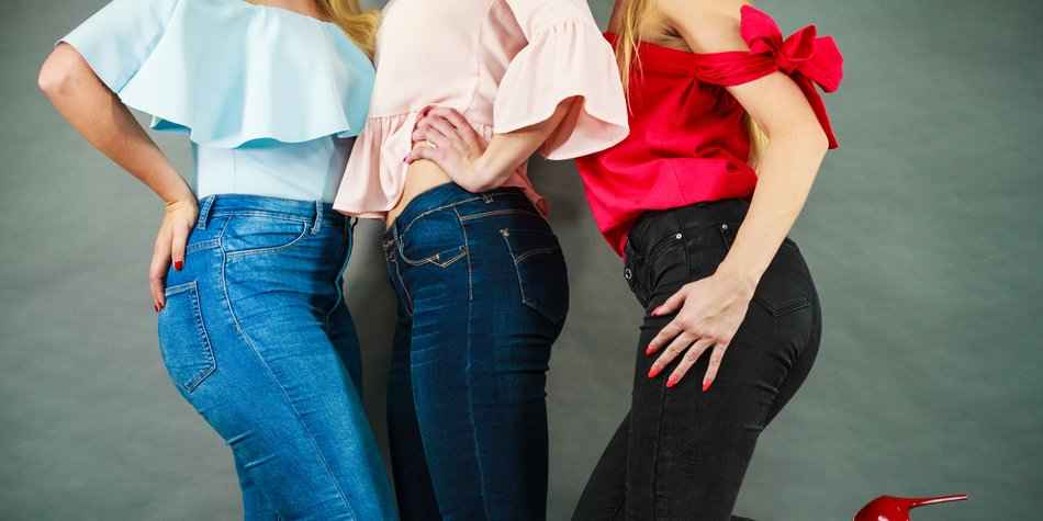 Three unrecognizable women having fashionable outfits, blue jeans and colorful shirts. Fashion and clothing concept.