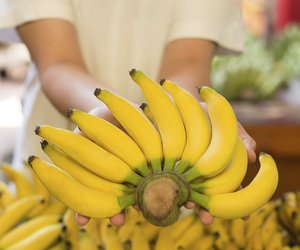 Hand holding yellow bananas in the market