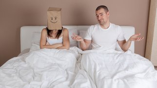 Funny situation in bed. Young couple lying in bed and woman with paper bag over head