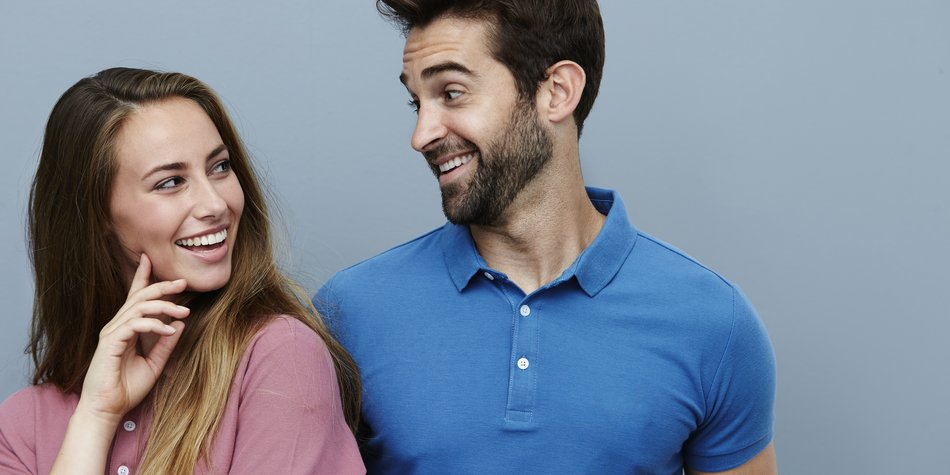 Couple smiling at each other in polo shirts
