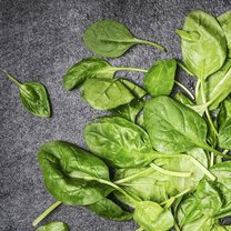Fresh spinach leaves on dark wooden background, top view