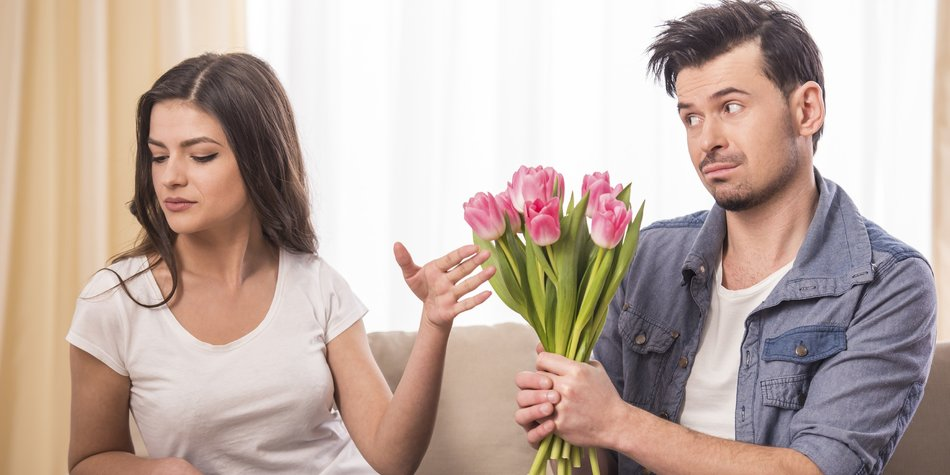 Young man is offering a bunch of flowers to his angry girlfriend at home.