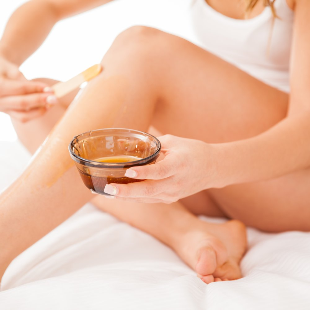 Young woman with beautiful legs putting some wax on them to remove all their hair
