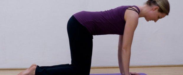Schritt 1 der Pilatesübung Leg Pull Front bei der die Pilateslehrerin die Gesäßmuskeln strafft.