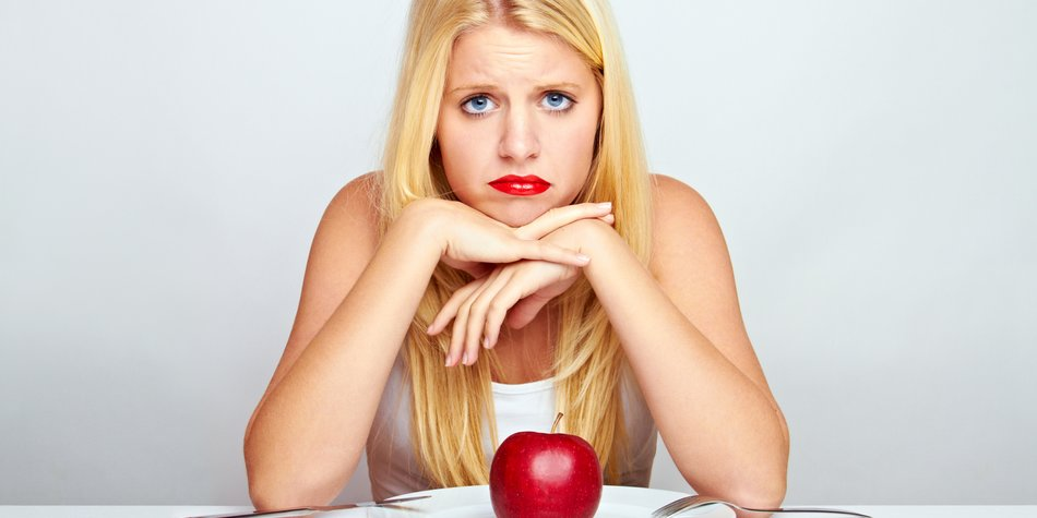 young blond woman with red apple on a plate with silverware