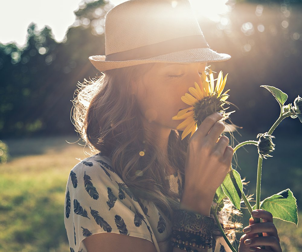 Girl smells sunflower in nature