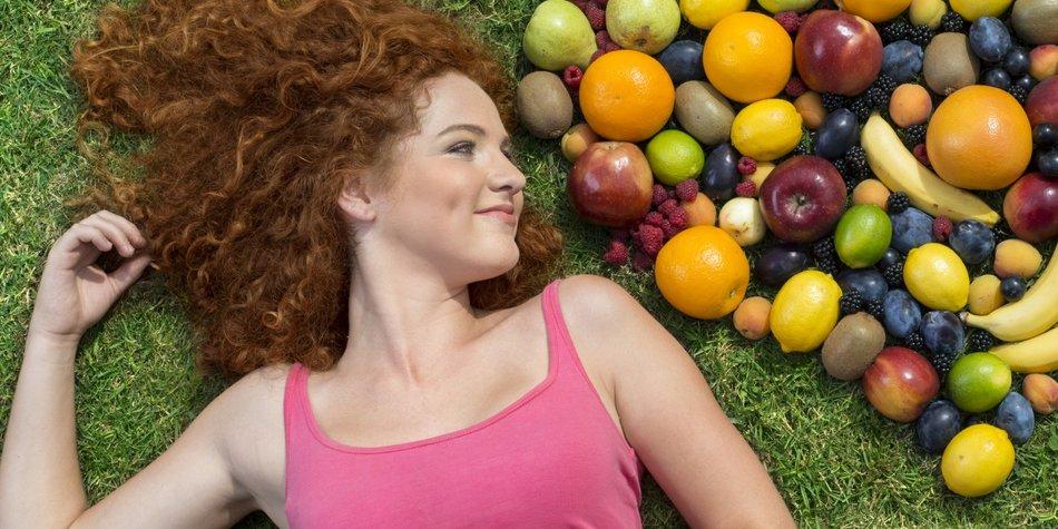 Ein Mädchen liegt aus einem Herz aus Obst
