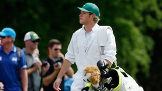 AUGUSTA, GA - APRIL 08: Niall Horan of the band One Direction works as a caddie for Rory McIlroy of Northern Ireland during the Par 3 Contest prior to the start of the 2015 Masters Tournament at Augusta National Golf Club on April 8, 2015 in Augusta, Georgia. (Photo by Ezra Shaw/Getty Images)