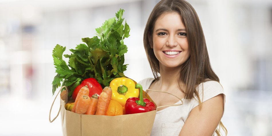 Woman holding a shopping bag full of fresh food