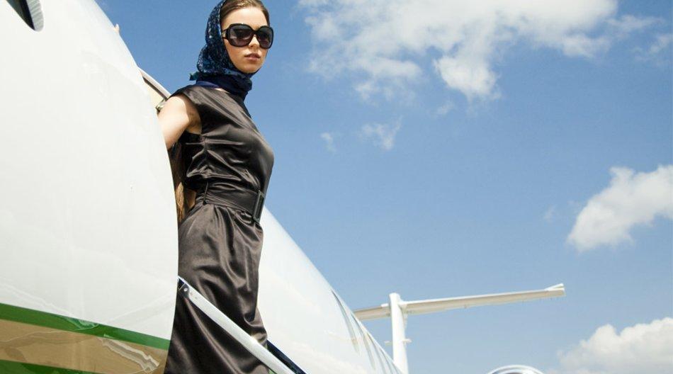 Frau posiert vor einem Flugzeug