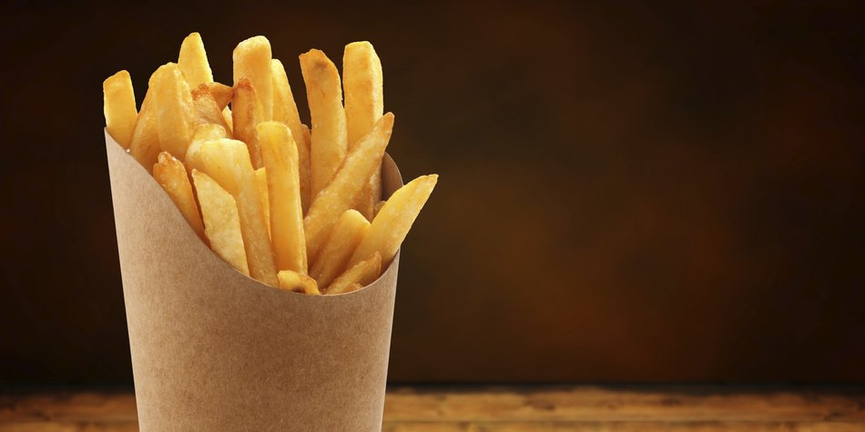 french fries in a paper basket on wooden table