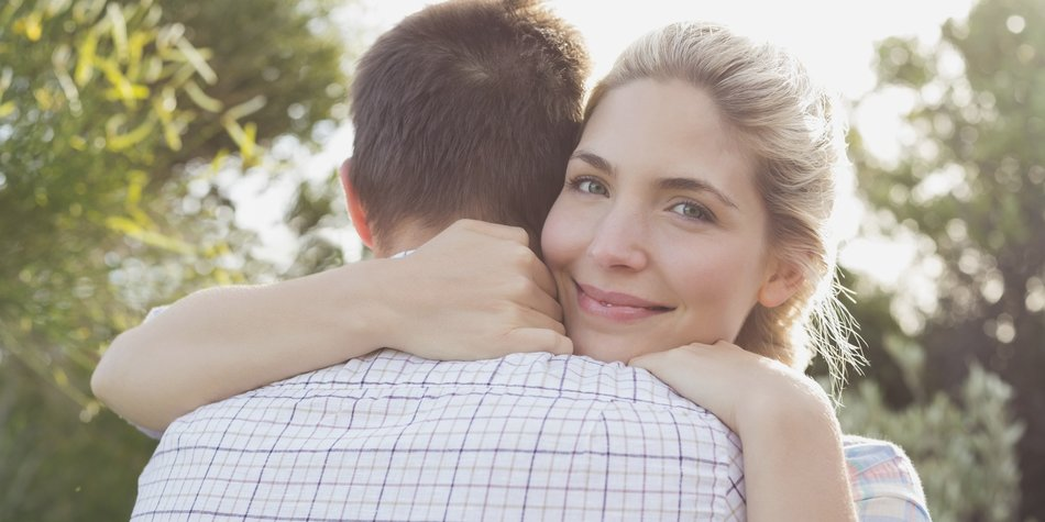Close-up of a smiling young couple embracing in the park