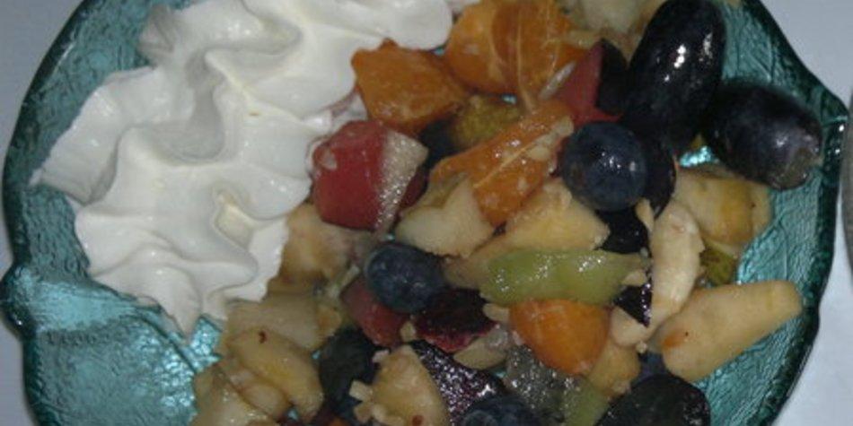 Bunter Obstsalat mit gehackten, gerösteten Haselnüssen, getrockneten Cranberrys und Sahne