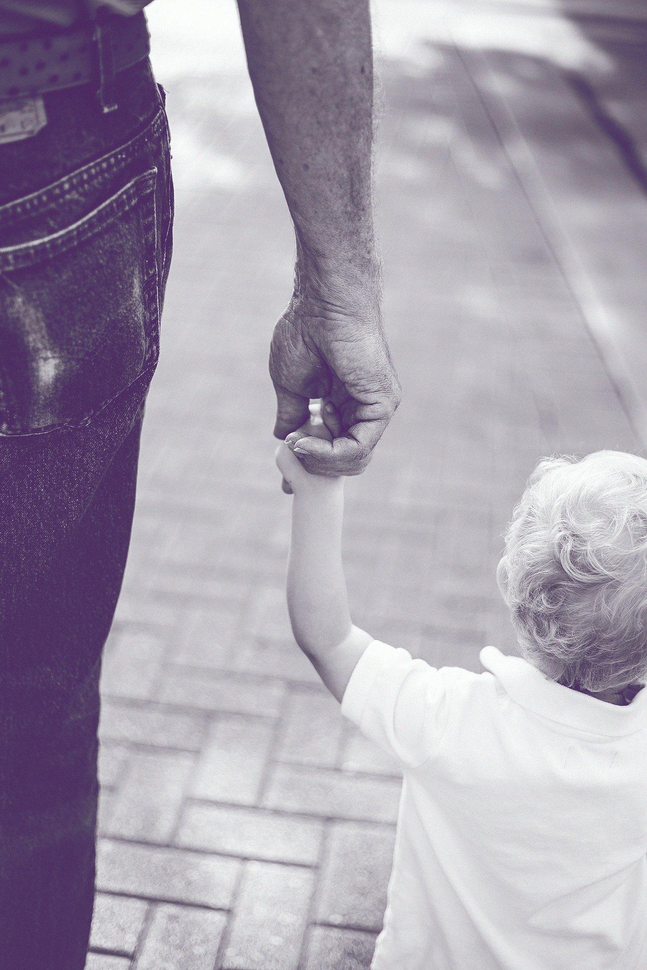 Vater hält seinen Sohn an der Hand