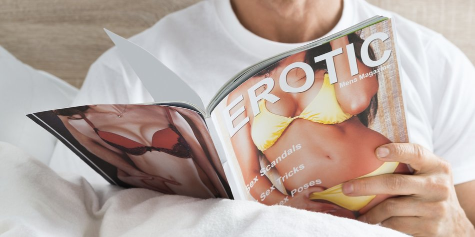 Close-up Of A Man Holding Magazine At Home