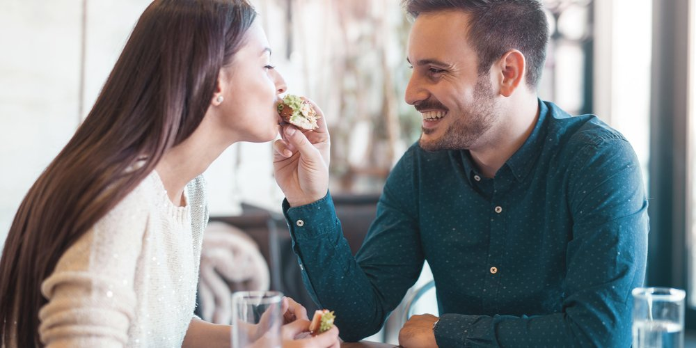 Dating in a cafe. Happy loving couple enjoying breakfast in a cafe. Love, romance, relationships, food, lifestyle