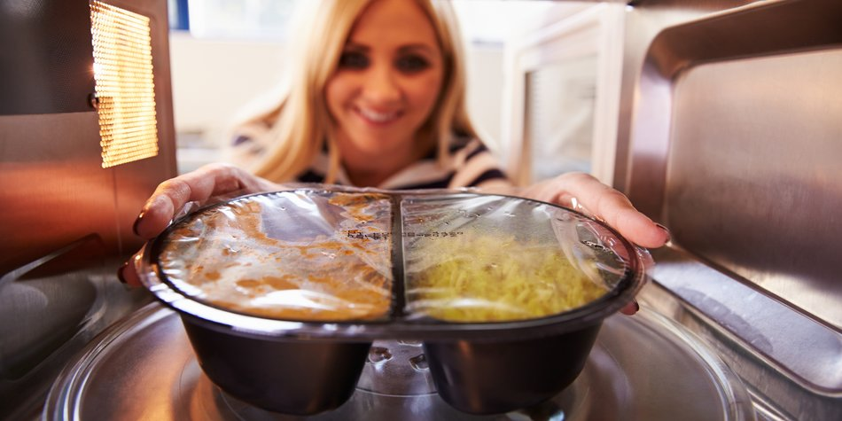 Woman Putting TV Dinner Into Microwave Oven To Cook. Smiling