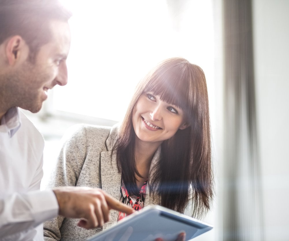 Young businessman and businesswoman using digital tablet in office