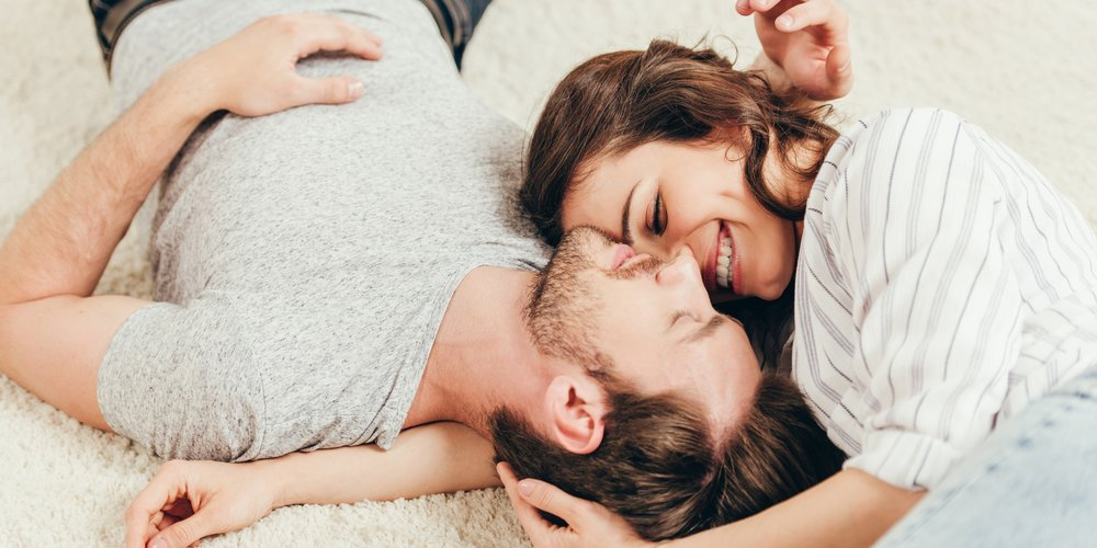casual young couple embracing while lying on carpet at home