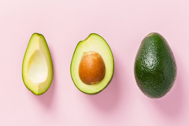 Ripe avocado - whole and cut fresh green fruit with seed on pastel textured backdrop. Close up flat lay photography of organic tropical food for healthy eating concept.