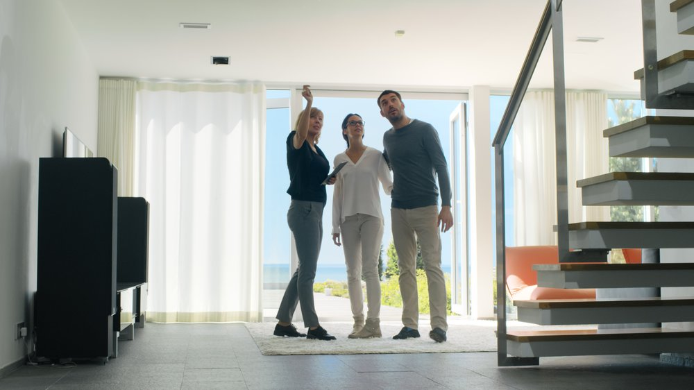 Professional Real Estate Agent Shows Stylish Modern House to a Beautiful Young Couple Who are in the Market for Purchasing/ Renting New Home. House Has Floor to Ceiling Windows and Seaside View.