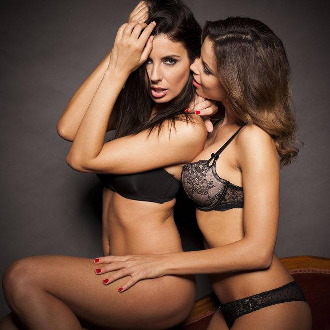 Sexy lesbian couple in lingerie on gray isolated background