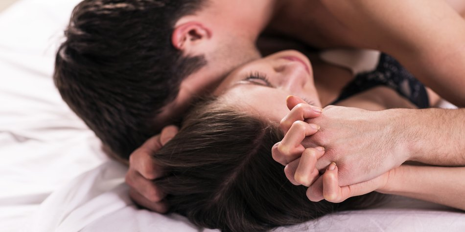 young lovers kissing on the bed focused on hand