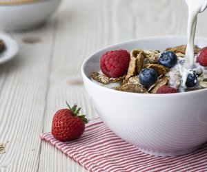 Pouring milk into the bowl with multigrain natural flakes with blueberries and raspberries