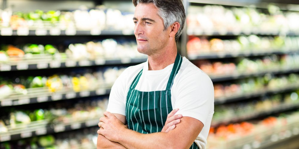 Thoughtful seller with arms crossed in supermarket