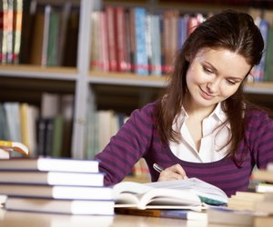 Portrait of charming student getting ready for report in college library